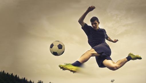 Liikkuva nuori keltaisissa nappiksissa potkaisee vauhdikkaasti jalkapalloa
