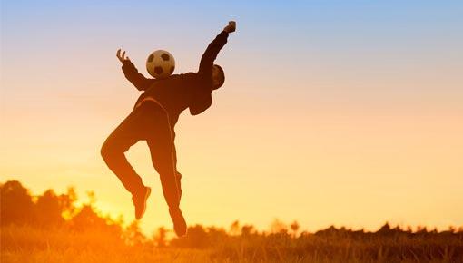 Liikkuva nuori auringonlaskun aikaan ottaa jalkapallon vastaan rintakehällä