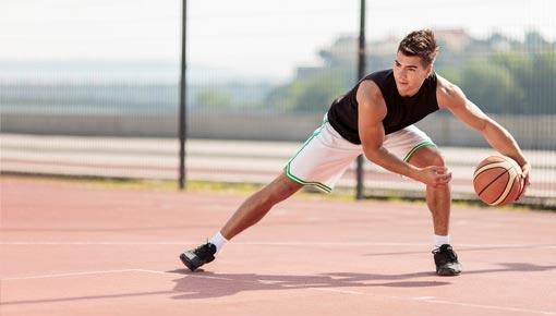Liikkuva nuori koripalloilija harjoittelee koripallonkäsittelyä ulkokentällä