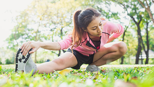 Paljon liikkuva tummahiuksinen tyttö venyttelee pohjetta vehreässä puistossa