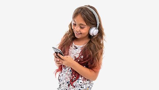 Ruutuaikaa noudattava iloinen ja hymyilevä pitkähiuksinen tyttö katsoo kännykkää valkoiset kuulokkeet korvillaan