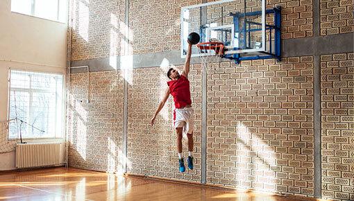 Liikkuva nuori koripalloilija donkkaa koripallon koriin kaupunkimaisemassa city-kentällä